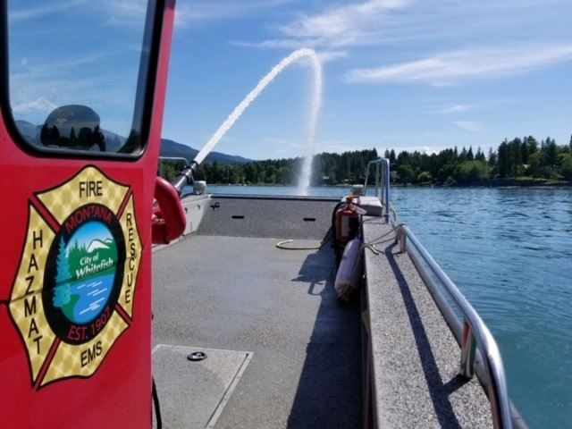 red fire boat, WFD logo, on lake spraying water off boat
