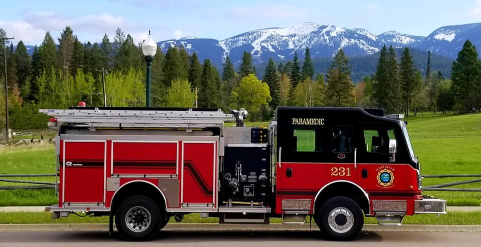 Red and black fire truck parked in front of mountain range