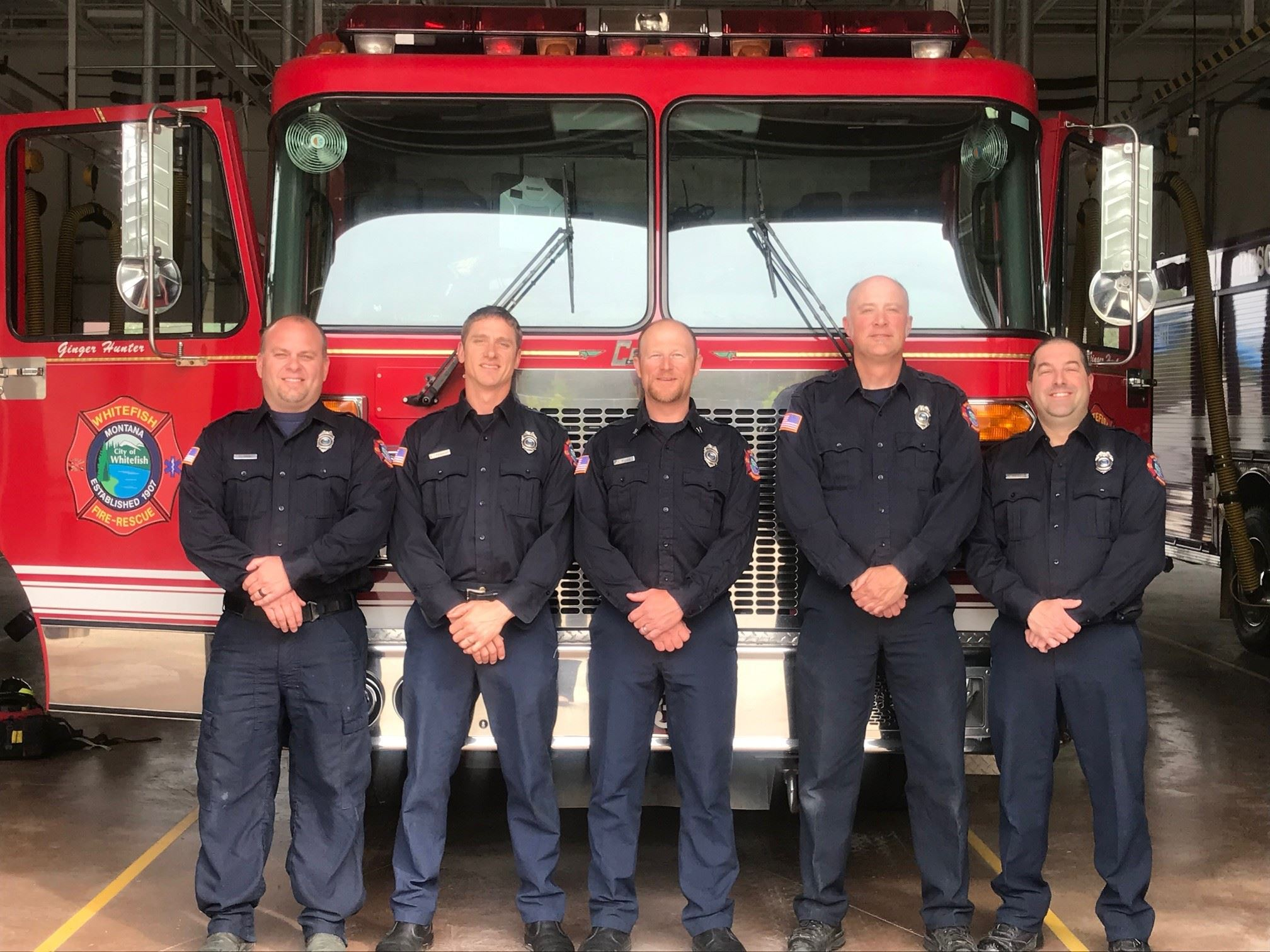 5 firefighter standing in front of a red and black fire truck