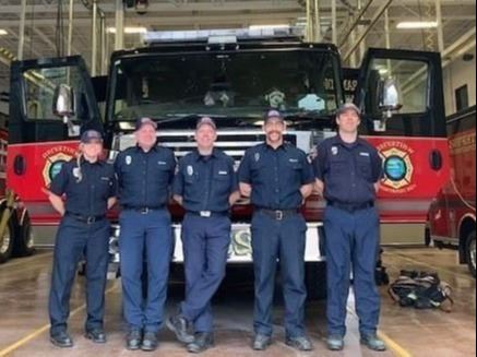 5 firefighters standing in front of a red and black fire truck